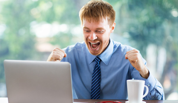 Young businessman sitting at table and looking at laptop screen while opening his mouth wide in excitement and pumping fists. Front view with big window and blurry green view outside in background.